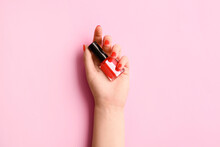 Woman With Beautiful Manicure Holding Bottle Of Nail Polish On Color Background