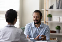 Focused Young African American Patient Discussing Illness Treatment With Skilled Indian Gp Doctor Physician, Telling Complaints At Regular Checkup Meeting In Modern Clinic Office, Healthcare Concept.