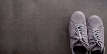Gray Sneakers On A Dark Background. Modern, Casual Footwear.