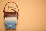 Fototapeta Kawa jest smaczna - Different stylish women's bags on pale orange background, flat lay. Space for text