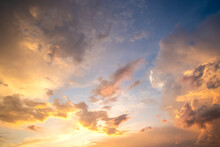 Dramatic Cloudy Sunset Landscape With Puffy Clouds Lit By Orange Setting Sun And Blue Sky.