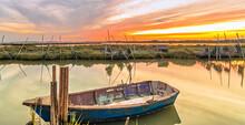 Vue D'une Barque De Pêcheur Et De Filets De Pêche Sur Les étangs En Camargue, France Au Coucher Du Soleil.
