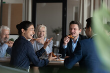 Excited Diverse Employees Eating Pizza During Break In Office Together, Happy Indian Businesswoman Laughing At Funny Joke, Talking Chatting With Colleagues, Having Fun, Sharing Corporate Lunch