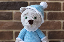 Knitted Teddy Bear In Blue Pajamas Against The Background Of A Brick Wall