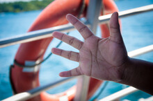 Closeup Shot Of An Open Hand On A Life Ring Background On The Boat