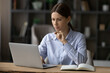 Leinwandbild Motiv Confident thoughtful woman looking at laptop screen, holding glasses, pondering strategy, sitting at desk, serious focused businesswoman or student working on online research project, studying