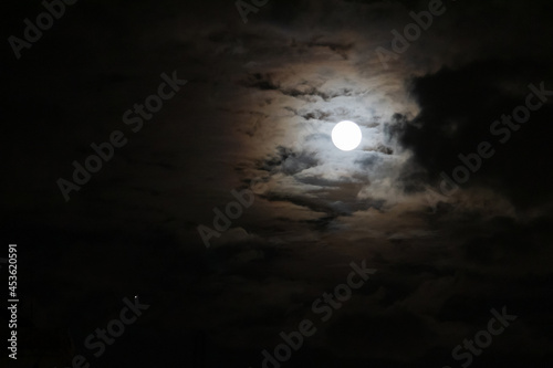 Fotografie, Obraz Full moon shining glowing light through the darkness of cloudy night sky; long exposure for beautiful nature background