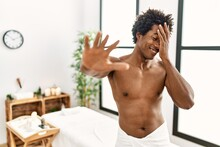 Young African American Man Shirtless Wearing Towel Standing At Beauty Center Covering Eyes With Hands And Doing Stop Gesture With Sad And Fear Expression. Embarrassed And Negative Concept.