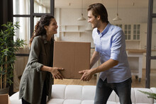 Happy Beautiful Young Family Couple Holding Big Cardboard Box In Hands, Moving Belongings In Renovated Living Room, Feeling Excited Of Purchasing Own Apartment, Real Estate Ownership Concept.