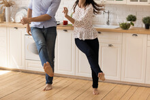 Focus On Barefoot Legs Of Happy Young Family Couple Dancing To Music On Warm Wooden Floor In Modern Renovated Kitchen, Joyful Millennial Man And Woman Homeowners Having Fun Together On Weekend.