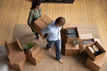 Above Top View Happy Young Barefoot Family Couple Homeowners Carrying Big Box With Stuff Into Renovated Stylish Living Room, Involved In Moving Own Belongings In New Apartment, Relocation Concept.