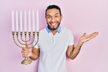 Hispanic Man With Beard Holding Menorah Hanukkah Jewish Candle Celebrating Achievement With Happy Smile And Winner Expression With Raised Hand