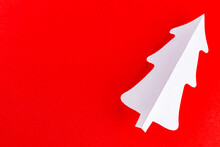 Paper Christmas Tree On A Red Background. White Paper Christmas Tree. Christmas Minimal Concept
