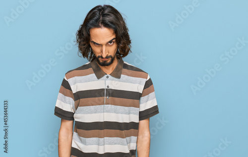 Fotografia Young hispanic man wearing casual clothes skeptic and nervous, frowning upset because of problem