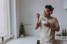 Young Happy African American Man 20s In Casual Clothes Headphones Listen Music Eat Breakfast Muesli Cereals With Milk Fruit In Bowl Prepare Cook Food In Kitchen At Home Indoor. Healthy Diet Concept