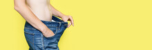 Concept Of Diet, Proper Nutrition, Weight Loss Slim Woman Showing Loose Jeans And Her Loss Weight. Woman In Oversize Jeans Isolated On Yellow Background Banner With Copy Space. Banner With Copy Space.