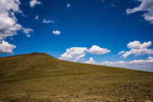 Green Mountain Hillside In Remote Area In The Rocky Mountains Against Blue Sky And White Clouds.