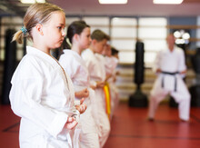 Group Of Girls And Boys In Kimono Doing Kata With Their Trainer In Gym.