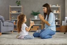 Happy Young Mother And Her Cute Little Daughter Playing Games Clapping Their Hands. Carefree Family Sits On A Warm Carpet On The Floor At Home In The Living Room And Have Fun Together.