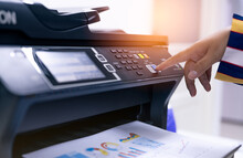 Office Worker Print Paper On Multifunction Laser Printer. Copy, Print, Scan, And Fax Machine In Office. Modern Print Technology.  Photocopy Machine. Document And Paper Work. Professional Scanner.