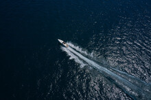 Large Boat On The Water In Motion Top View. Luxury Motor Boat On Dark Blue Water Aerial View. Travel On High-speed Boats On The Water. Speedboat Is Fast Moving In Dark Water.