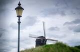 Fototapeta Na sufit - Holenderski wiatrak na pagórku oraz na tle pochmurnego nieba
