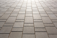 The Pedestrian Walkway Is Paved With Modern Concrete Paving Slabs Of Rectangular Shape But Of Different Sizes. Symmetrical Decreasing Perspective.