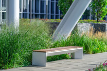 Empty Concrete Bench With Wooden Slats For Sitting On Tile Among Decorative Grass And Flowers In Recreation Area Near Modern Office Building. Garden Landscape With Chair In City Park