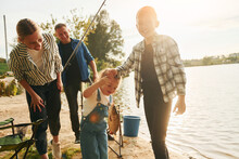 Big Catch. Father And Mother With Son And Daughter On Fishing Together Outdoors At Summertime