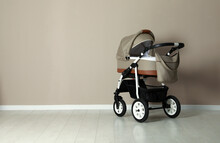 Baby Carriage. Modern Pram Near Beige Wall, Space For Text