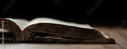 Obraz na plátně Image of an old Holy Bible on wooden background in a dark space with shallow dep