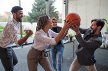 Group Of Cheerful Young Businesspeople Playing Basketball In Office, Taking A Break Concept.