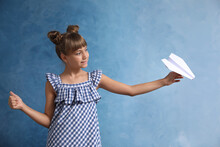 Cute Little Girl Playing With Paper Plane On Light Blue Background