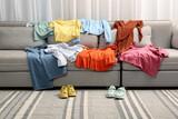 Fototapeta Kawa jest smaczna - Shoes near sofa with different clothes indoors