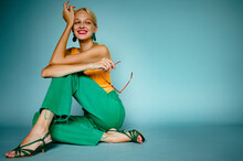 Happy Smiling Fashionable Woman Wearing Trendy Green Color Wide Leg Jeans, Strappy Sandals, Posing, Sitting On Blue Background. Copy, Empty Space For Text