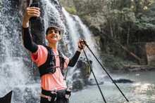 Traveling Man Taking Selfie Against Waterfall In Forest