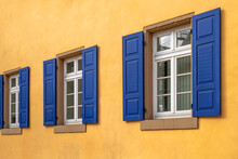 Three White Windows With Sandstone Sills In A Row With Dark Blue Shutters And A House Wall Painted Orange Yellow