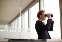 Businessman Using Binoculars At Office Window