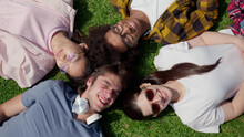 Top View Of Diverse Students Lying On Grass And Smiling