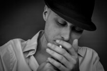 Black And White Portrait Of A Young Man With A Black Hat Intent On Lighting A Cigarette
