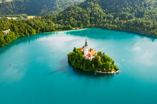Aerial View Of Lake Bled With Assumption Of Mary Pilgrimage Church On The Small Island On The Background Of Julian Alps In Slovenia