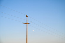 Concrete Pillar With Electricity Cables Hanging On. Electric Utility Pole With Power Lines With Moon In Background. High Voltage Electric Power Line Against The Blue Sky.