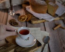Mão Segurando Xicara De Chá Em Mesa De Madeira Com Bolo Ao Fundo