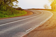 A Winding Road With Tire Tracks On The Asphalt. A Sharp Turn With Sunlight
