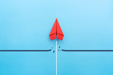 Red Paper Plane Breaking Through Obstacle On Blue Background, Concept Of Overcoming Barriers, Goal, Target