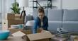 Leinwandbild Motiv Young woman unpacking in her new home