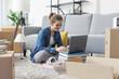 Leinwandbild Motiv Cheerful woman connecting online in her new home