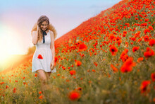 Beautiful Spring Summer Scenic Landscape. Happy Joy Cheerful Fantasy Woman Walking On Blooming Field Poppies. Red Flowers. Blonde Girl Look Down, White Vintage Short Dress. Backdrop Blue Sky, Sunshine