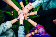 Young People Travellers Putting Their Hands Together. Friends With Stack Of Hands Showing Unity And Teamwork