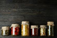Jars Of Pickled Vegetables On Rustic Wooden Background